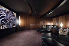 contemporary home theater room with black modern leather circular sofas