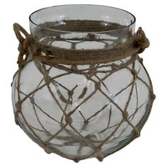 Add a rustic-chic touch to your entryway console table or living room mantel with this charming glass vase, showcasing a netted twine accent. $16