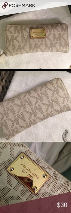 Michael Kors wallet. White MK wallet. Good size, there's a change compartment in the middle, enough room on either side of the compartment for money, cash, receipts, has spots on both sides for cards. The gold Logo plate is a little scratched, and there's stain on the side of the wallet, in otherwise good condition. Accessories