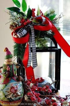 Lantern with greenery and ribbon.  Love the black and white checked ribbon added in with the red….something different.