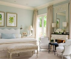 A serene bedroom, made so partly by the soft cool colors.The draperies bought to just below the crown molding draws your attention to it & adds to the visual height. And there's something about a fireplace in a bedroom that is really appealing.