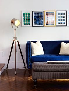 Closeup of living room seating arrangement. A high-arm tufted blue velvet settee is paired with white cashmere cable-knit pillows, modern geometric prints, and a tripod lamp. Designed by Chango & Co.