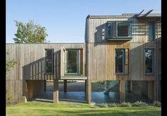 Modern flint and timber-clad house above a coastal floodplain in Burnham-Overy-Staithe.