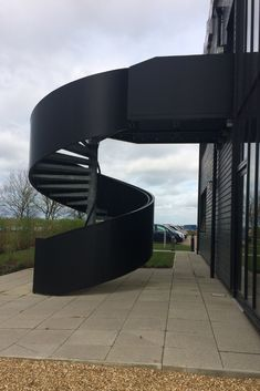 An escape spiral staircase for Incubator Building at Alconbury Weald Enterprise Campus. The full height black balustrade really makes an impact. Spiral Staircase Outdoor, Black Staircase, Staircase Design, Spiral Staircases, West Elm Chandelier, External Staircase, Exterior Stairs, Stairs Architecture, Fire Escape