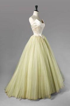 Balenciaga pour EISA Haute Couture, circa 1953. Robe de bal. Satin duchesse champagne avec découpe arrondie figurant une pointe de chaque côté, rappel sur la petite basque, jupe longue en tulle de soie absinthe (griffe blanche, graphisme gris)