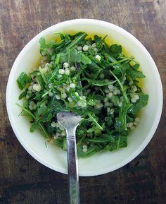 couscous & arugula salad     1 cup israeli couscous  4 - 6 cups arugula, torn  1/2 english cucumber  3 green onions, sliced    juice of 1 lemon  1/4 cup olive oil  1 clove garlic, minced  1/2 teaspoon dijon mustard  1/2 teaspoon agave syrup  1/2 teaspoon aleppo pepper (or 1/8 teaspoon crushed red chilis)  1/4 teaspoon kosher salt