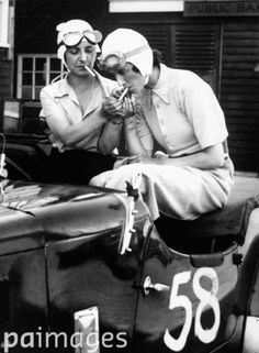 Mrs Gordon Simpson and the young Australian racing driver, Joan Richmond, sitting in Miss Richmond's 1921 3-litre G.P. Ballot racer, partaking in a cigarette before the start of a race. 7th July 1934