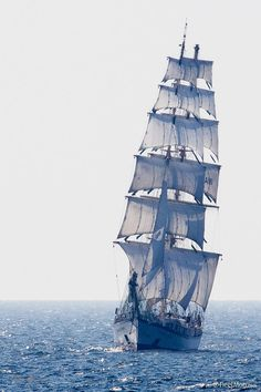 A fine, tall ship towering above the quiet sea