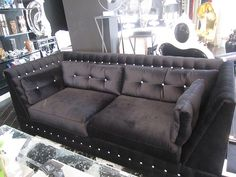 4197 BLACK VELVET SWAROVSKI CRYSTAL SOFA  Custom made with an extremely durable hardwood frame and gorgeous descending corners, this sofa is fabulously made. It is upholstered in a brilliant black velvet that is complemented beautifully by the matching cushions and the dazzling array of Swarovski crystals. This sofa is the perfect way to glam up your house.  96 in (Width) 41 in (Depth) 37 in (Height)