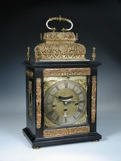 Sale F261114 Lot 596  William Speakman, London, a double basket top three train bracket clock, with alterations, the ebonised case with 4 turned finials above and repousse gilt metal mounts, the 7inch (18cm) dial with winged mask spandrels, mock pendulum and date aperture, silvered chapter ring, signed to a rectangular brass strip above the dial, having verge escapement, chime silent lever, the well engraved backplate signed 'Wm Speakman London', chiming and...  - Cheffins