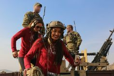 A Washington Redskins cheerleader smiles after firing an M240B Machine Gun while visiting soldiers attached to Combined Joint Special Operations Task Force-Afghanistan while at a range near Kabul province, Afghanistan, 2014