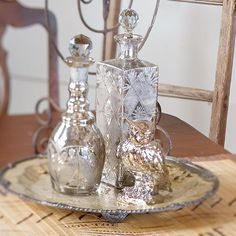 Potion Glassware Arrangement ~ Add some toil and trouble to your Halloween display by grouping antique perfume bottles on a bronze serving platter to look like magic potions. Stick to just one color of glassware or mix golds, silvers, and bronzes for monochromatic magic.