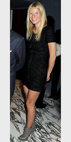 Gwyneth in a black mini dress and gray stiletto booties.