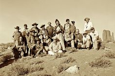 John Wayne, Jeffrey Hunter, Danny Borzage—who played accordion on Ford's film sets for four decades— and more of the cast and crew of The Searchers gather around director John Ford on set in Monument Valley.