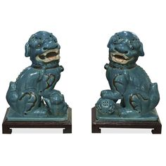 Always standing in pairs, Foo Dogs are fantasy lions in Chinese mythology who serve as guardians to prevent harmful things from happening to the family. This handsome pair are standing in commanding posture. The male, with a paw on a symbolic ball, protects the world, while the female, with a paw on a cub, protects the dwelling. Hand crafted in porcelain with over all blue glaze. Great to display on a mantel or side table as a symbolic Asian accent. Sold in pair, matching wooden stands sold…