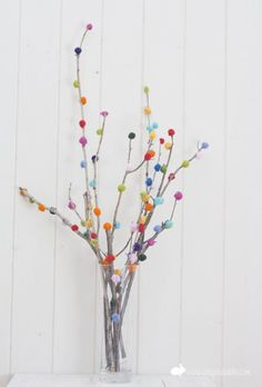 DIY pom poms project for winter: Bare tree branches look festive with multicolored pom poms. Use in a clear glass vase as a fun, wintertime centerpiece.