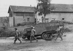 1944, France, Bruyères, Des soldats US passe près de la carcasse d'un blindé de allemand de prise française Zugkraftwagen P107 U304 (f) (Unic-Kégresse P107)