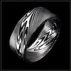 Thor Damascus Steel Men's Wedding Ring. Andrew Nyce Designs offers this unique contemporary metal men's wedding band composed of distinctive swirling layers of Damascus stainless steel with the Thor pattern and a black oxide coating.
