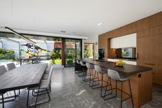 Large kitchen/dining/family area with large black frame sliding doors , opening directly out to alfresco/pool area Interior Designers Melbourne, Sliding Doors, Building Design, Large Black, Kitchen Dining, House Design, Contemporary, Frame, Table
