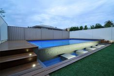 This symmetrically designed geometric pool ties in seamlessly with the contemporary style of the residence and the clients modern taste. Featuring an infinity edge finished in large format cladding the shallow spillover trough lends itself perfectly to the large stepping stones constructed across the length.  LED strip lighting beneath the trough decking highlight the water wall and