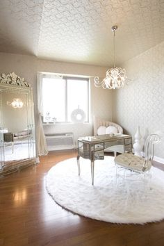 Feminine rooms can be sleek and straightforward too. The touches of shine, rounded shapes and nods to coziness in the rug and cushion are what make this relatively spare room a ladylike one.  Gorgeous mirror!