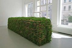 """""""Mona Hatoum's constantly changing installational sculpture at the gallery of Berlin's DAAD artists program. Hatoum had 770 jute sacks stacked up to head level; the resulting pile is 10 meters long and resembles the sandbag barricades used in battle as shelter from enemy gunfire"""" """"... the sacks are filled with seeds that continue sprouting throughout the duration of the exhibition."""""""