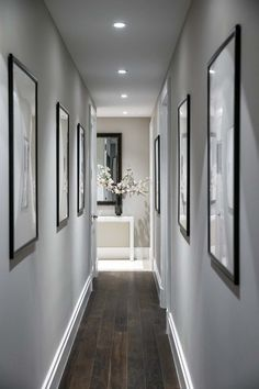 Modern contemporary hallway design and decor. Grey hallway walls, hardwood floors and bright LED recessed lighting. Hanging pictures in a narrow hallway. Hallway Wall Decor, Hallway Walls, Upstairs Hallway, Entryway Decor, Entryway Ideas, Grey Hallway Paint, Hallway Entrance Ideas, Flat Hallway Ideas, Hall Way Decor