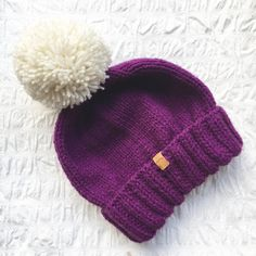 Hand-knitted bobble hat in a magenta purple yarn with cream bobble. Unisex fit. Knit in aran wool with a close stitch to give a nice neat fit. Finished with a faux leather Junkbox label & can be worn any way round. Colour may vary slightly as each hat is handknit from a different ball of yarn. 80% acrylic 20% wool
