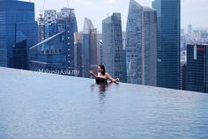 Infinity Pool with a glass of wine and skyscrapers in the background