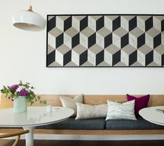 """Balance graphic statements with softer, more organic patterns. Here, we created a custom art piece by framing a bold patterned fabric and mounting it to the wall,"" says Nelson. ""Then we paired it with more organic textiles to soften the look. We also balanced the hard lines of the banquette with the curves of the chairs and oval tables."""