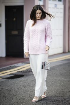 Anisa Sojka wearing pink Three Floor knit, white ASOS wide-leg trousers, mirrored silver Skinny Dip summer clutch bag, gold My Flash Trash rings, and white Zara heels. Street style shot in London by Cristiana Malcica.