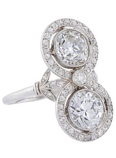 A French Toi et Moi Diamond and Platinum Two Stone Ring.  Vertically millegrain set with cushion-shaped stones estimated to weigh 3cts each, within a frame of circular-cut stones, between trefoil shoulders, bearing French control mark on shank. Circa 1915.