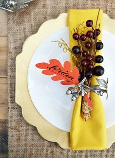 Decorative faux berries anchor a paper leaf place card and bright, gold napkin together. Click through to get the tutorial and see more easy DIY Thanksgiving place cards! #thanksgivingplacecardsdiy #thanksgivingplacecardideas #easythanksgivingplacecards #thanksgivingplaceholdersdiy
