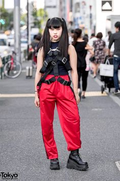 17-year-old Japanese high school student Sarah on the street in Harajuku wearing a sleeveless Drinkscancode top with harness, resale striped pants, Demonia platform boots, a resale Eastpak crossbody bag, and tattoo necklace from Faith Tokyo. Full Look