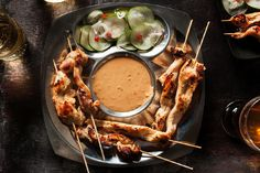 An easy recipe for grilled chicken that's been marinated in coconut milk and red curry, served with peanut sauce and simple, spicy cucumber pickles.