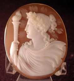 Museum Quality Carved Cameo of Nike, circa 1860. Seldom seen & very large at 1 3/4 x 2 1/4 Has the c & t pin. The setting is 9 ct. Nike holds the torch of the Olympians. Even the folds in her dress are high relief