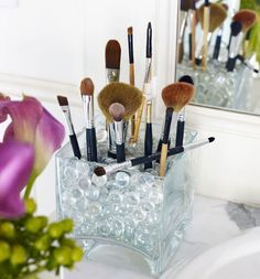A contemporary square vase filled with glass marbles makes a spiffy container for makeup brushes.