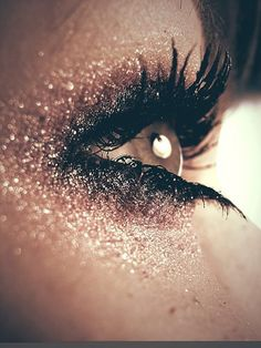 Dramatic eye makeup using different colour gradients of glitter eye shadow.