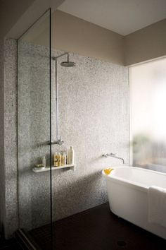 This freestanding tub is within a wet-room/large shower area.  Via #Remodelista.