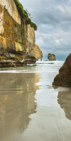 Tunnel Beach, Dunedin, New Zealand. Tunnel Beach has sea-carved sandstone cliffs, rock arches and caves. Dunedin is in the South Island of New Zealand, and the principal city of the Otago Region.