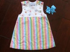 One-of-a-kind handmade girls dress size 2T/3T made with a cotton white sleeveless bodice and a multi-colored skirt with vertical stripes of yellow, green, red, turquoise. The dress is fully lined. Comes with a matching turquoise grosgrain clip bow. Sweet colorful flower buttons adorn the bodice.
