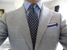 Grey windowpane suit, patterned tie, pocket square, blue striped shirt