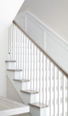 The staircase features a clean, neutral look thanks to the square white spindles and white oak handrail and flooring. Patterson Custom Homes. Brandon Architects, Inc. White Staircase, Staircase Design, Cottage Staircase, Spiral Staircase, Oak Stairs, House Stairs, Transitional Living Rooms, Transitional House, Transitional Bathroom