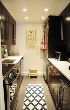 Galley style kitchen. Love the graphic rug. I need a small stepper like this one permanently in my kitchen.