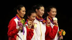 Gold medalists Na Li, Xiaojuan Luo, Yujie Sun, Anqi Xu of China and their coaches celebrate on the podium during the medal ceremony after the Women's Epee Team Fencing Finals on Day 8