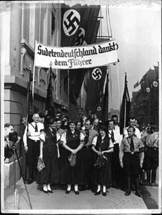 "Sudeten Germans hold banner that reads ""Sudetenland thanks Führer."" Berlin. 1.10.1938."