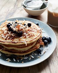 Coconut Pancakes Recipe. For brunch chef Adam Schop sprinkles shredded coconut onto his pancake batter; when the pancakes cook on the griddle, the coconut gets nicely toasted. The finished pancakes get a layer of extra coconut before serving.