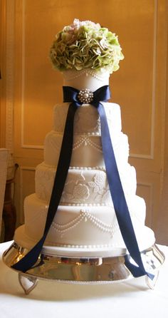 white five tier wedding cake with floral addition and navy blue ribbon with brooch