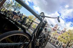 Canales de la ciudad de Amsterdam Holanda.  Amsterdam es indudablemente especial. Ya no solo por sus coffee shops su famoso barrio rojo o sus canales... Sino también por el notable número de bicicletas que hay en la ciudad.  Se podría decir que  Amsterdam es la capital de las bicicletas. Posee más bicicletas que habitantes. Ya que tiene más de 1 millón de bicis frente a los 700.000 ciudadanos que la habitan.  Los altos costes por estacionamiento y sus complicados callejones convierten a la…