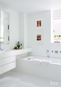 In the all-white, airy master bathroom, the tub is by Hastings Tile & Bath; the tiles are by Ann Sacks. The framed images are from the collection Twelve Photographs by Stephen Shore.
